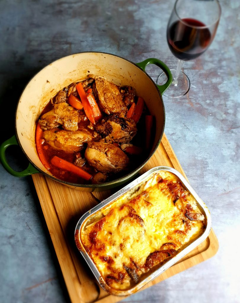 Takeaway food from Goodies Food Hall - showing a bowl of casserole, potatoes dauphinois and a glass of red wine